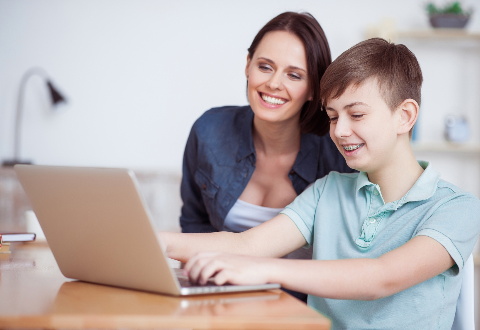 Happy mother helping his son to do homework